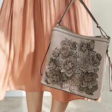 Model holding flower handbag