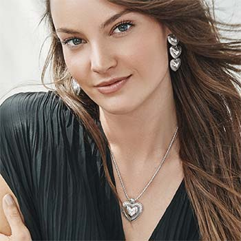 Model wearing heart pendant necklace and earrings