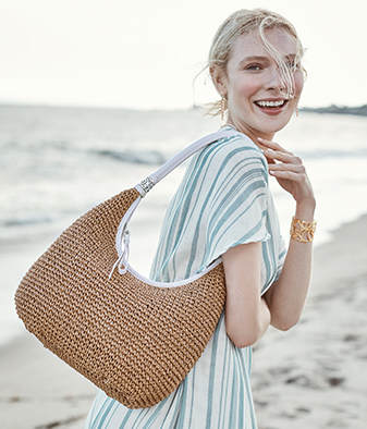 model on the beach wearing straw bag