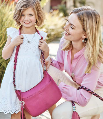 mother and daughter wearing barbados handbags in pink