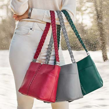 Brighton Model holding three different color bags