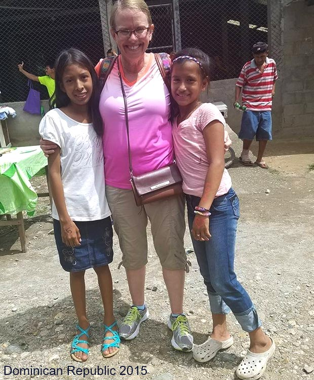 Brighton Employee visits with kids receiving shoes in Dominican Republic